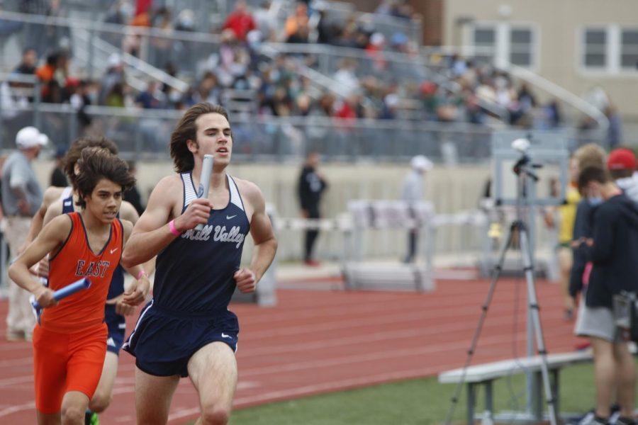 Gripping the baton in his hand, senior Karch Crawford leads Olathe East in the 4x800m relay.