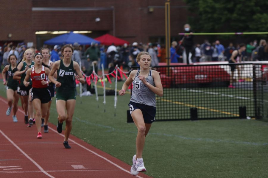 Leading the in the 1600m race, junior Bridget Roy rounds the corner of the track to start her third lap.