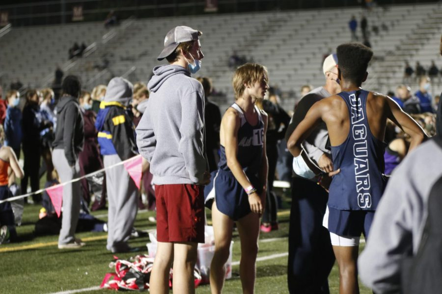 Gathered on the infield with other teammates, senior Cameron Coad and freshman AJ Vega discuss how the 3200m race went.