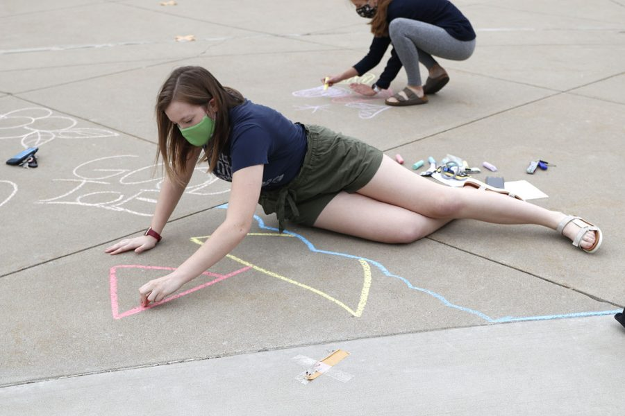 Creating a sailboat, NHS officer Taylor Moss uses various colored chalk to make her artwork vibrant.