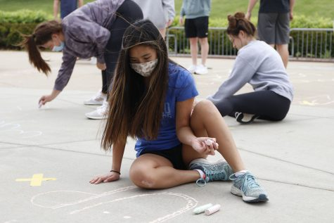 Glancing at her artwork, NHS member junior Jada Eggleston plans out what shes going to write next to elementary students at Prairie Ridge Elementary School on Monday, May 3.