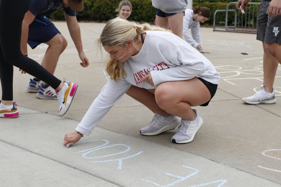 Writing with chalk, NHS member senior Landry Haydock shares a positive message for students.
