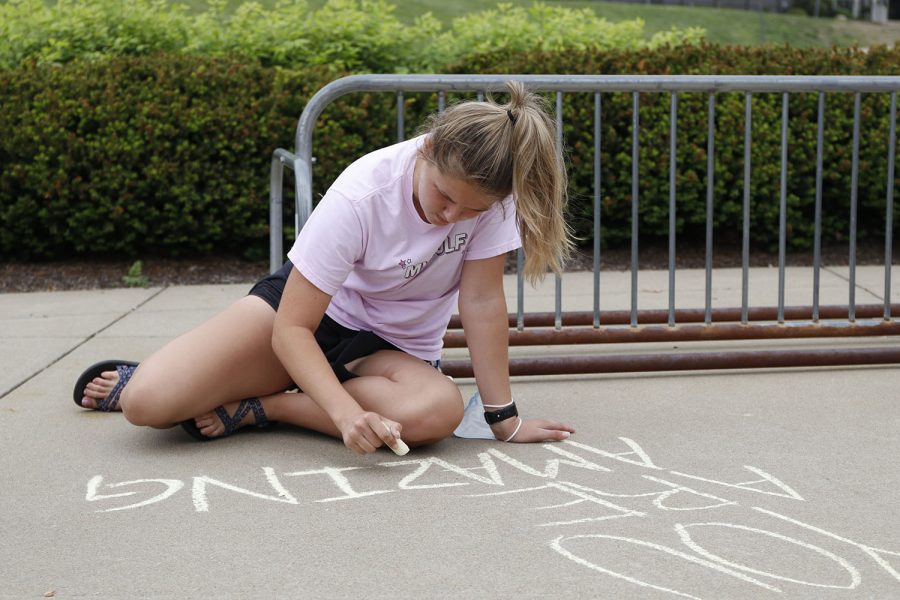 Using chalk, senior Meagan Haymaker, as part of NHS, writes the message