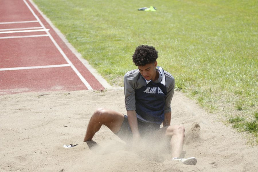 Hitting the sand, junior Adrien Dimond looks down to see how far he marked in the triple jump. Dimond would go on to get first place in triple jump with a final distance of 43-07.75 feet and first place in long jump with a final distance of 21-08.75 feet.