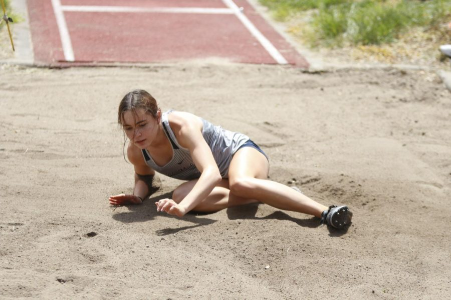 Hitting the sand, senior Lily Fleetwood looks to see how far she marked in the long jump. Fleetwood placed 7th in the third flight with a final distance of 16-02.00 feet.