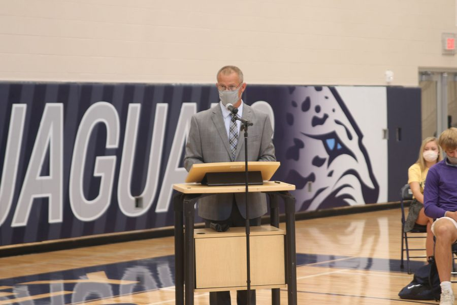 Standing at the podium in the main gym, athletic director Jerald VanRheen announces how the ceremony will proceed.