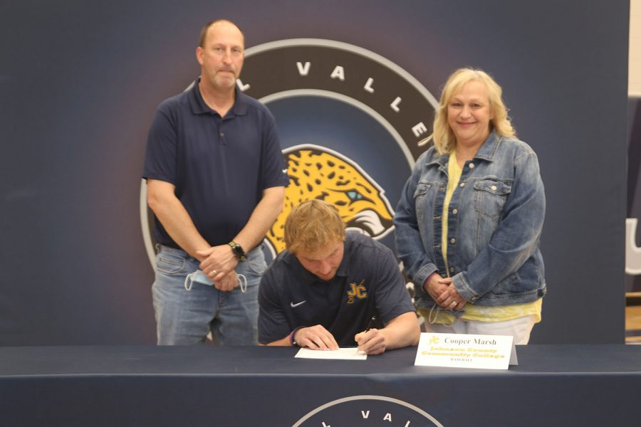 Senior Cooper Marsh signs and poses with his parents. Marsh will attend Johnson County Community College for baseball.