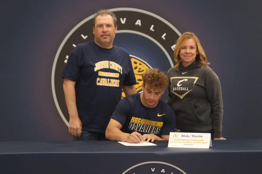 Senior Blake Martin signs and poses with his parents. Martin will attend Johnson County Community College for baseball.