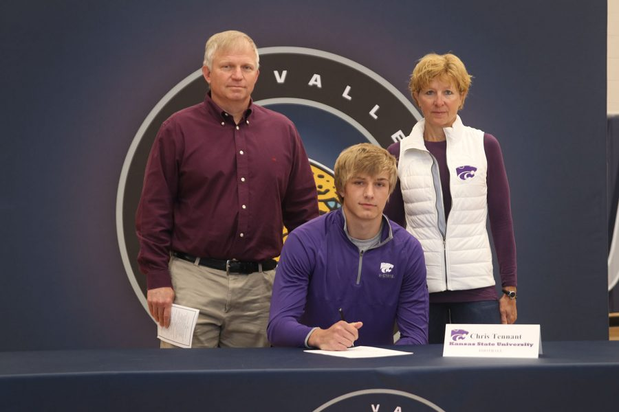 Senior Chris Tennant signs and poses with his parents. Tennant will attend Kansas State University to play football.