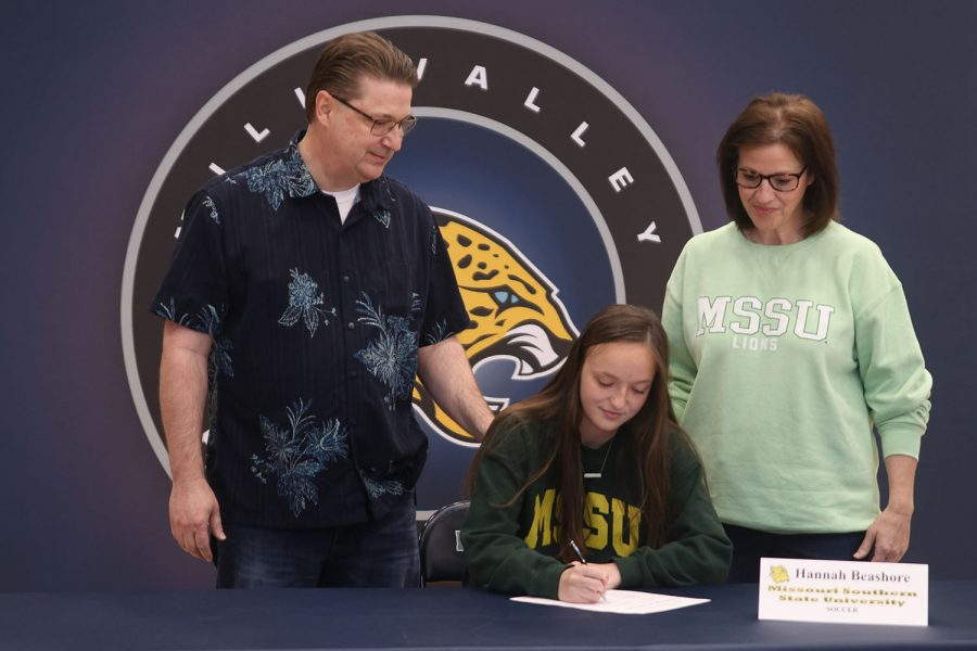 Senior Hannah Beashore signs and poses with her parents. Beashore will attend Missouri Southern State University for soccer.