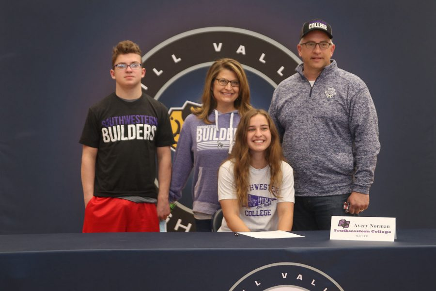 Senior Avery Norman signs and poses with her parents. Norman will attend Southwestern College for soccer.