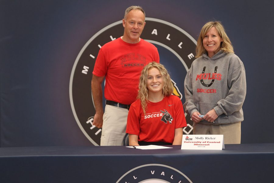 Senior Molly Ricker signs and poses with her parents. Ricker will attend University of Central Missouri for soccer.