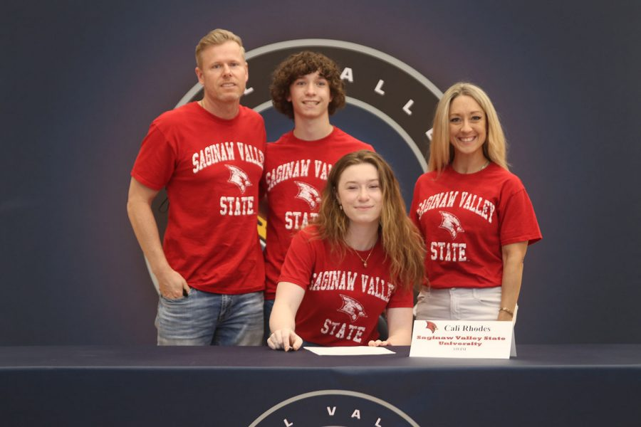 Senior Cali Rhodes signs and poses with her parents. Rhodes will attend Saginaw Valley State University for swim.