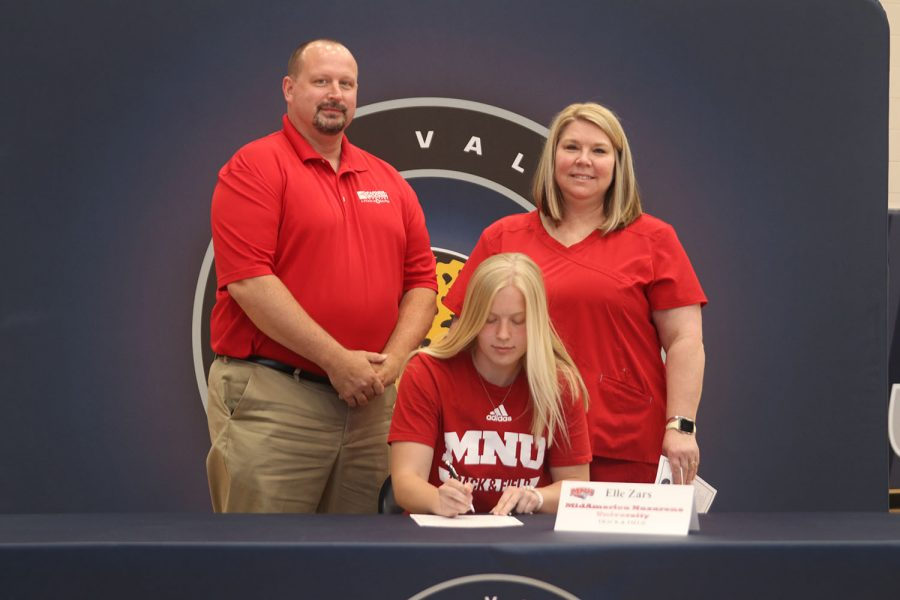 Senior Elle Zars signs and poses with her parents. Zars will attend MidAmerica Nazarene University for track and field.