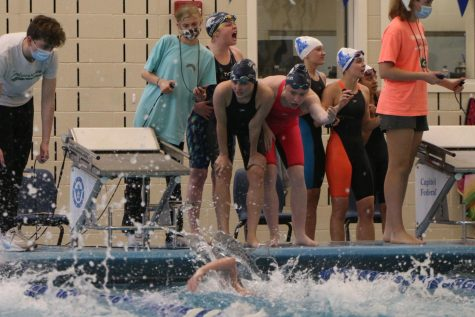 Focusing on the race, the 200-yard freestyle relay team encourages freshman Ella Hansen as she swims her leg at the state meet Saturday, May 22. The team placed fourth overall.