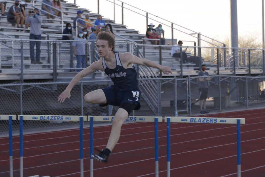 Arms out, sophomore Finn Campbell clears the second to last set of hurdles in the 300m hurdle race.