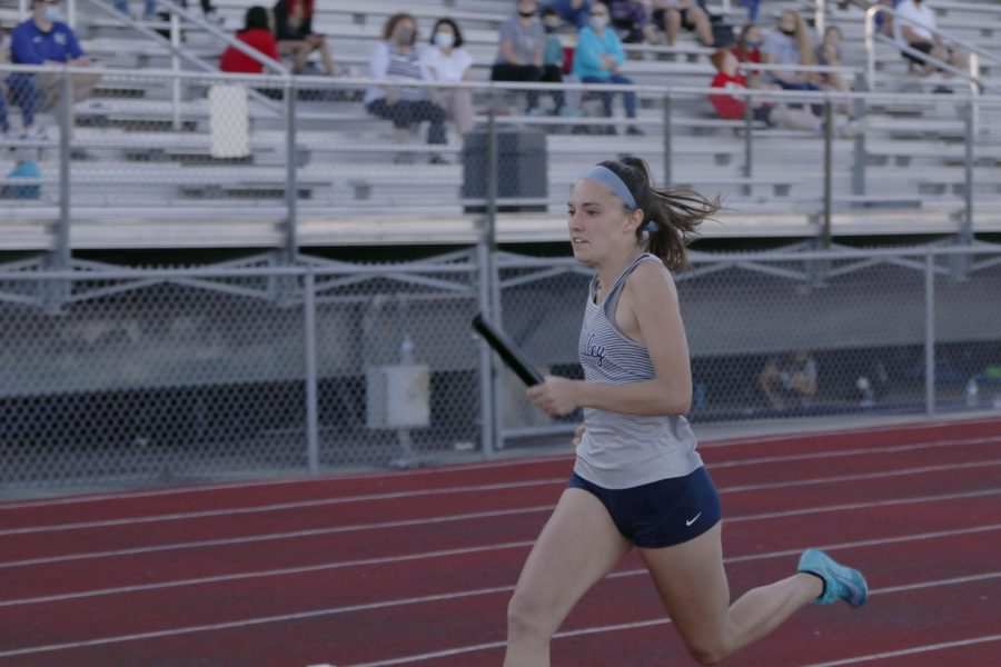 Baton in her hand, senior Peyton Wagoner runs the anchor leg of the 4x100m relay. The relay teams placed 4th,