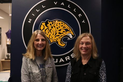 Next to each other, secretary Edie Waye and math teacher Laurie Deuschle stand in front of the jaguar in the office.