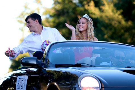 With a smile on his face, Homecoming king candidate senior Nick Brubeck throws candy from the car to the children on the side of the road while his partner Homecoming queen candidate senior Avery Davis waves to the crowd.