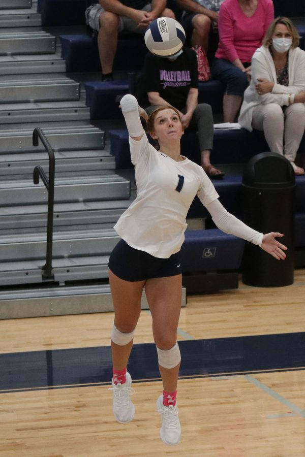 In the air, senior Brylee Peterson prepares to hit the ball over the net.