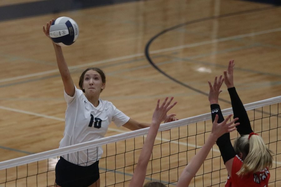 As opponents prepare to block her, senior Reese Johnston hits the ball over the net.
