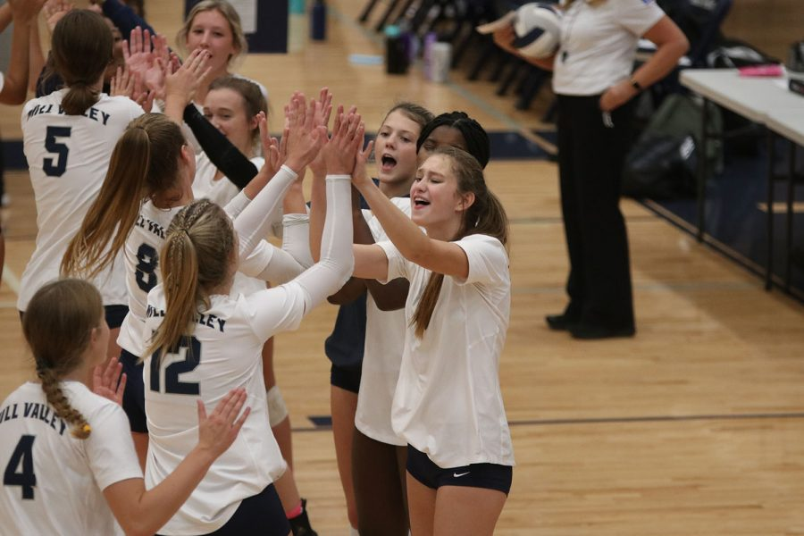 As the starting players run onto the court, the rest of the varsity team high fives and cheers.