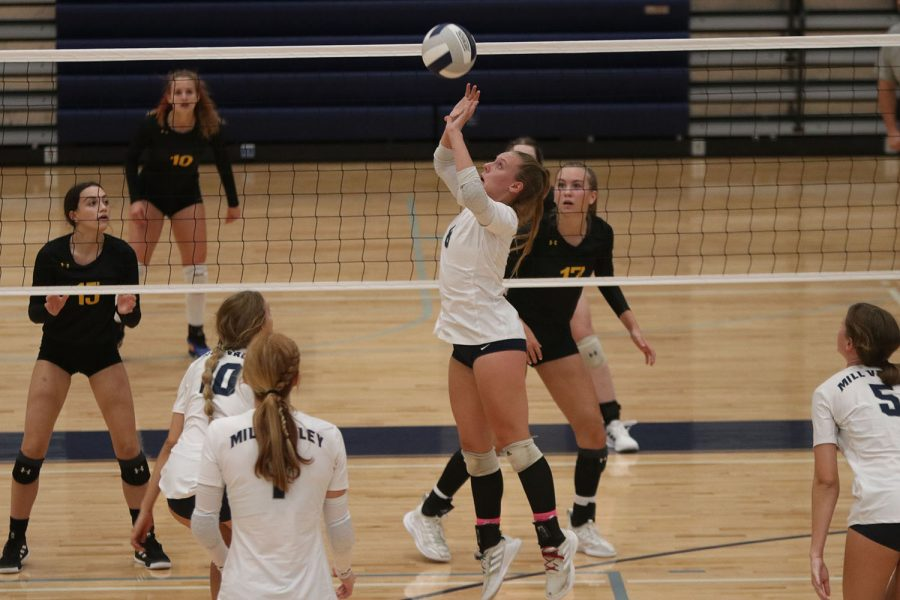 While her teammates prepare to hit, senior Sydney Fiatte sets the ball.