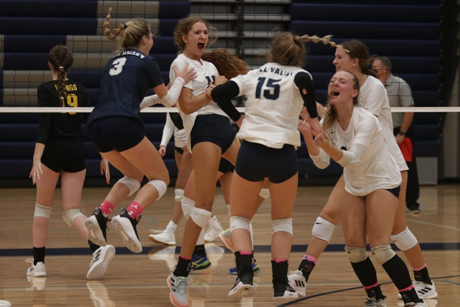 After winning a point, the volleyball team celebrates on the court during the triangular against BVW and SMW Thursday, Sept. 2. They beat each team in the first two sets. The first home game brought a large crowd of student supporters.