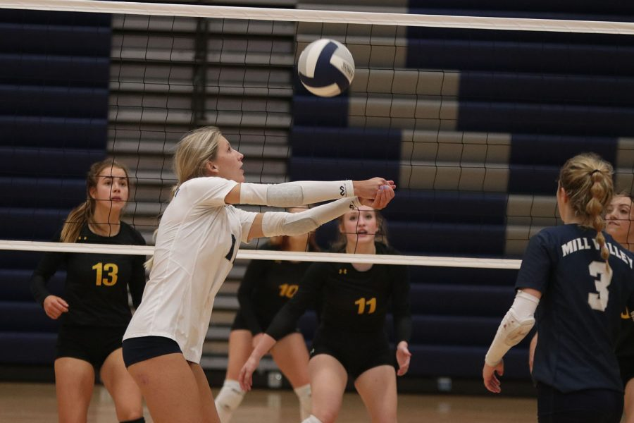 Next to the net, senior Kate Roth passes the ball.