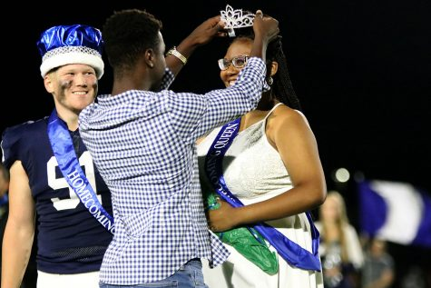 While the crown is being placed on her head, Homecoming queen senior Hannah Hunter gazes ahead at the cheering crowd Friday, Sept. 24. Hunter stands beside Homecoming king senior Cody Moore as she is being crowned by the former Homecoming king Quin Witternauer.