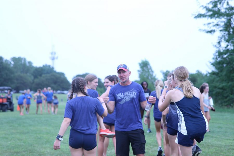 Before the girls team is called to the chute for the start of the race, head coach Chris McAfee fist bumps each runner.