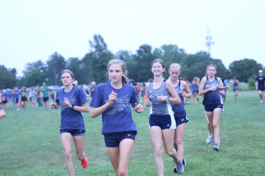 Before the race, senior Bridget Roy leads the varsity girls team in pre-race warm ups.