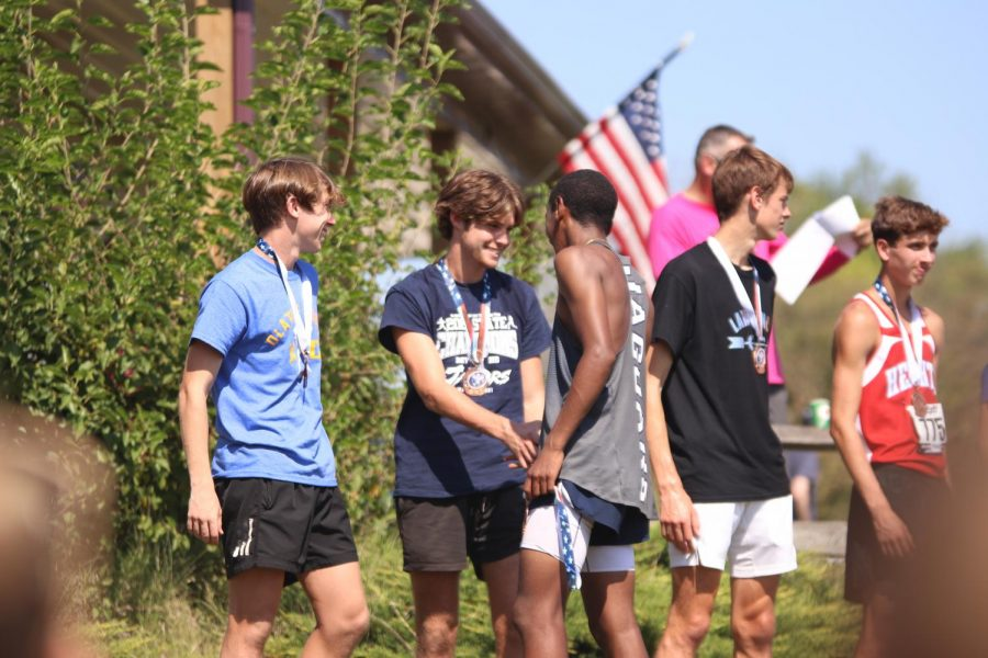 Smiling at one another, freshman AJ Vega shakes hands with senior Chase Schieber before taking his spot among the other medalists.