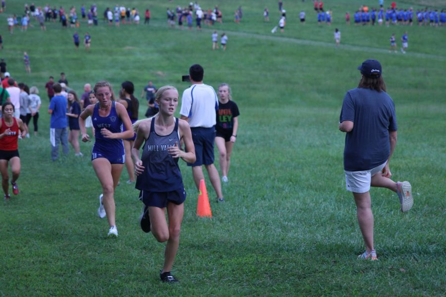 Leading her competitor from Olathe West, freshman Charlotte Caldwell runs up a hill. Caldwell placed eighth overall in the varsity girls 5k race.