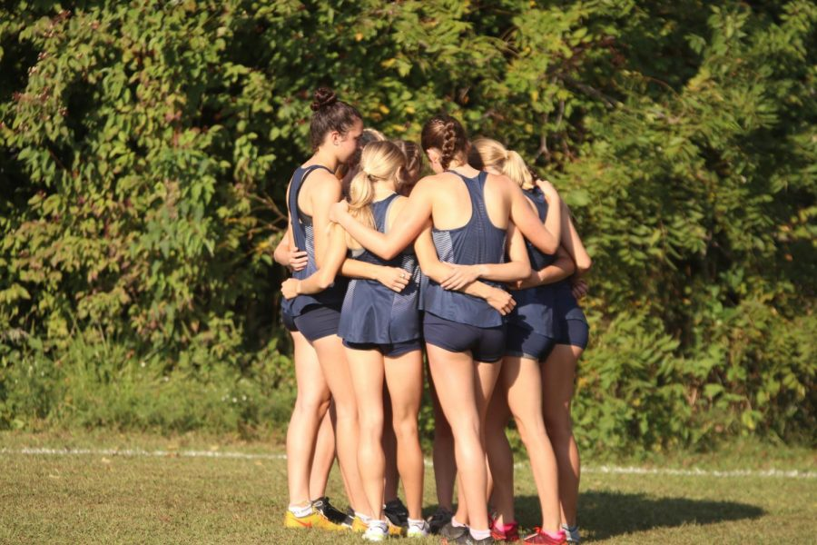 The girls varsity team huddles with one another before their race.