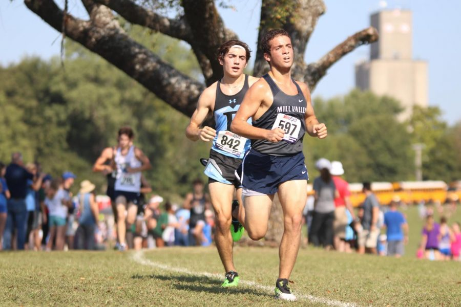 In the heat of the mid-morning, senior Vinny Bruno takes big strides to lead Shawnee Mission runner Ben Rodriguez.