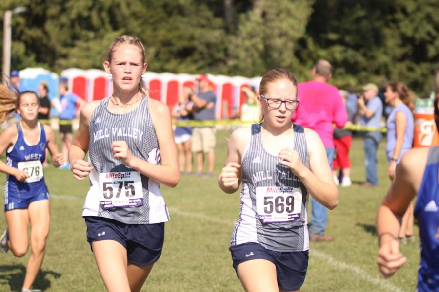 Running next to each other, freshmen Calista Marx and Laura Hickman finish their first mile. Marx and Hickman took 5th and 2nd respectively in the girls JV race.