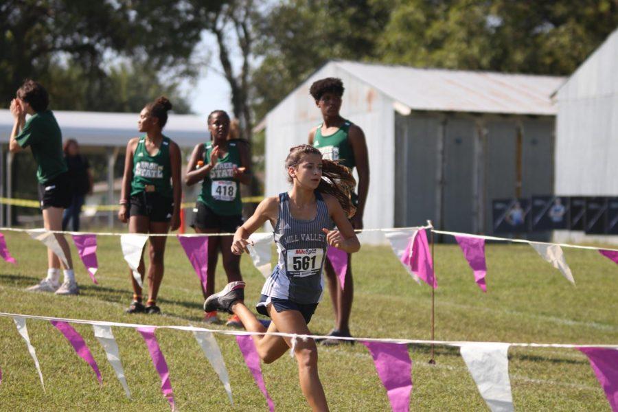 Freshman Isabel Cherrito races through the flags toward the marked finish line.