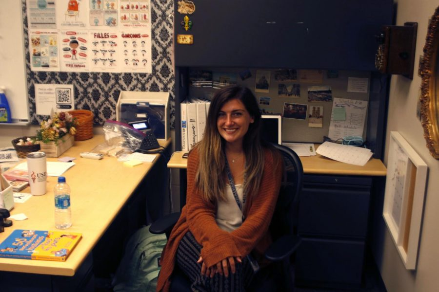 French teacher Michelle McRay sits at her desk in front of all her photographs that each hold their own significant meaning