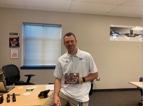Business teacher Adam Runyan holds a picture of his family in front of his desk. Runyan looks forward to creating a great environment for his students while also building the girls basketball program.