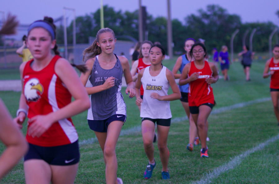 Looking to the side, freshman Maggie Wieland stays in between two runners.