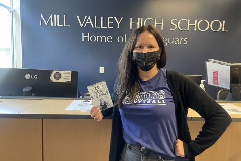 Holding a photo of her son, secretary Ashley Witherspoon poses at her desk in the front office. She is looking forward to football season and getting involved with other sports.