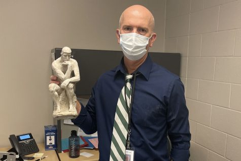"""Soccer coach and social studies teacher Jason Pendleton holds a statue of """"The Thinker"""" he has displayed in his classroom. Pendleton looks forward to """"building positive relationships with kids""""."""