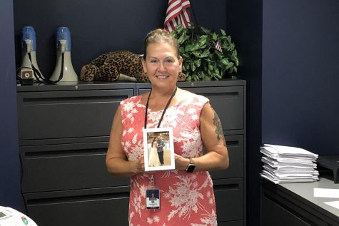 Athletic secretary Linda Logan poses with a photo that was taken of her and her father at her wedding. Logan is excited to help as many people as she can this year.