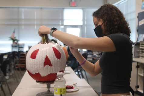 Touching up her pumpkin, junior Alex Cobin works on finishing up her final layer of white.