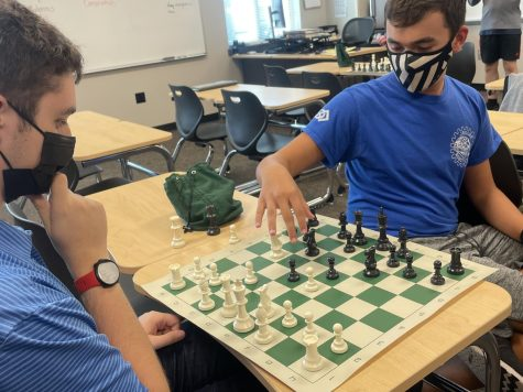 Junior Isaac Steiner makes his move while Senior Colin Keltner watches, thinking about his strategy