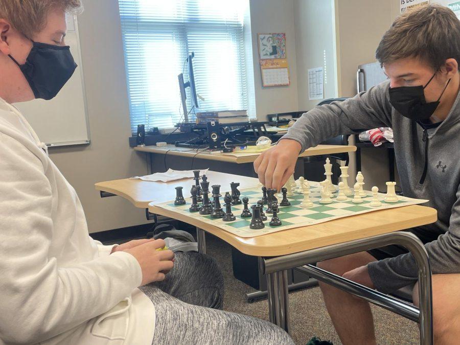 Junior Connor Bauer watches as his classmate, junior Gabe Martin makes his next move