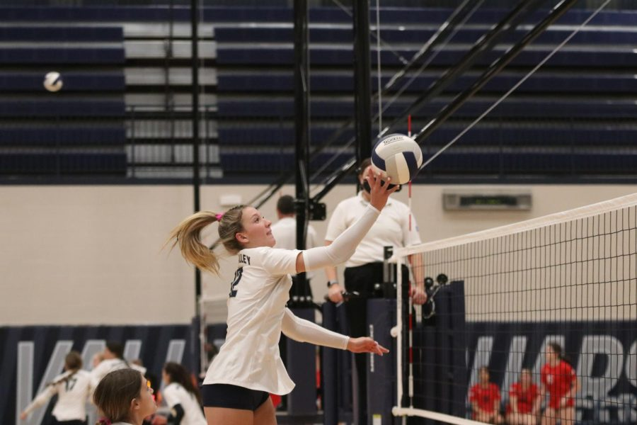 Jumping up, junior Madeline Schnepf stops the ball, sending it back toward Shawnee Mission North.