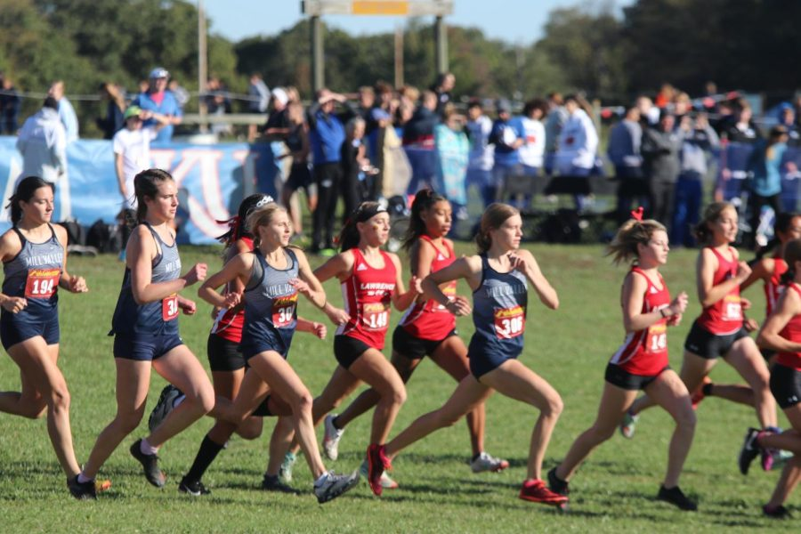 The girls cross country team runs off after the starting pistol was shot. The teams ran at Rim Rock Farms Saturday, Oct. 16 for the Sunflower League conference meet, where the boys placed fourth and the girls placed third.