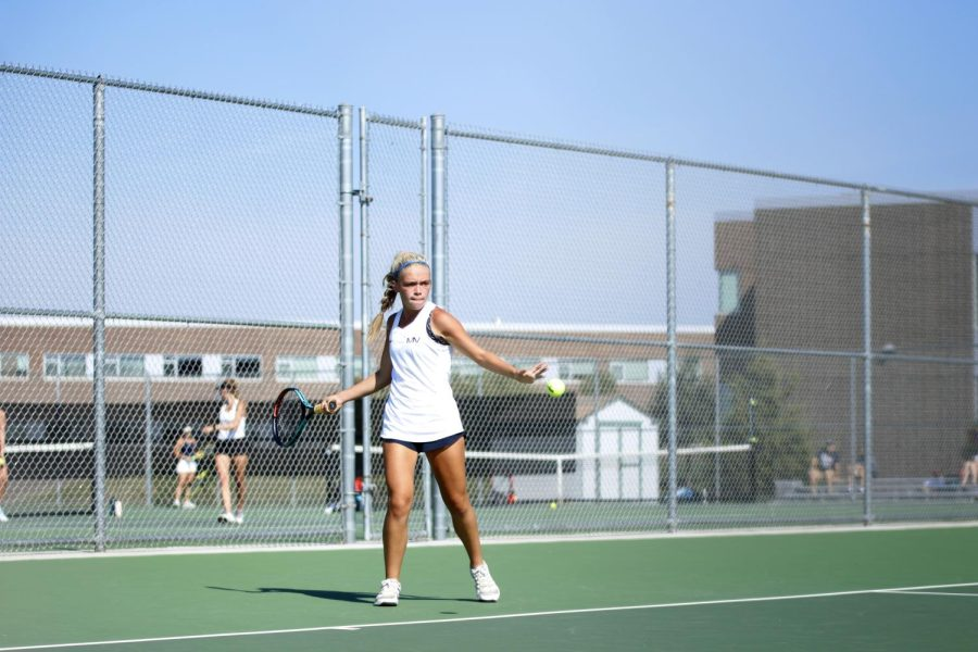 Ready to hit the ball, junior Bri Coup holds her racket.